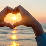 corazon de manos en playa