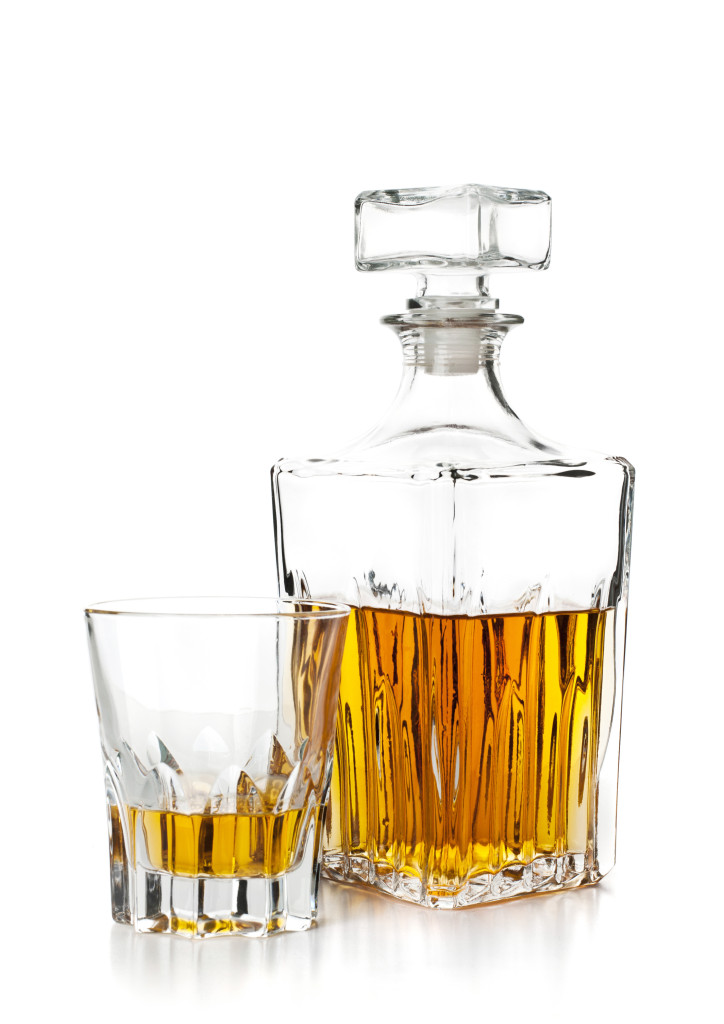 bottle and glass of whiskey on white background